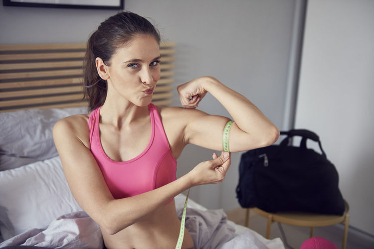 Portrait of woman measuring bicep with tape measure on bed at home