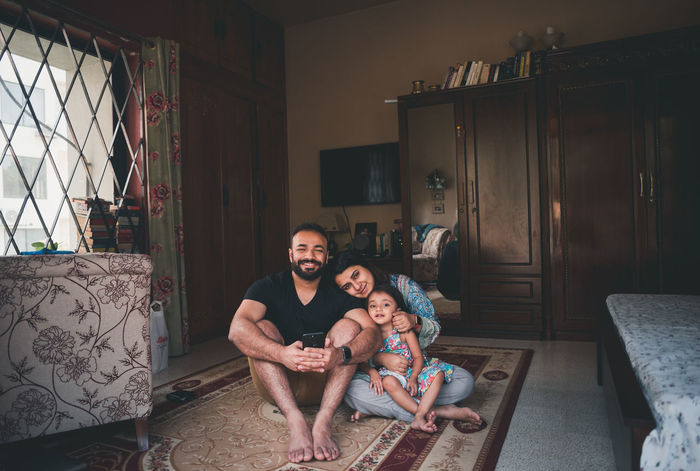 Portrait of smiling parents sitting with daughter on carpet in living room at home