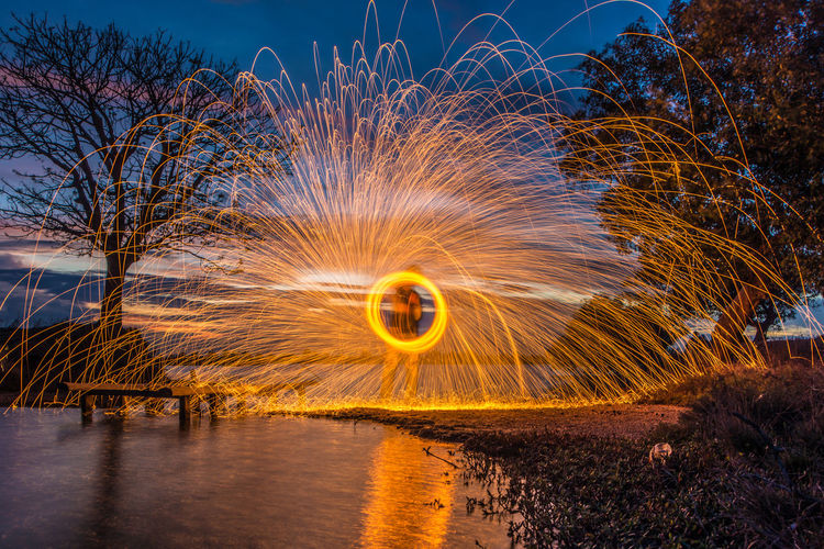 playing Wire Wool Tree Galaxy Motion Long Exposure Fireball Yellow Water Sky Entertainment Light Painting Firework Light Sparkler Fairy Lights Spinning Light Trail