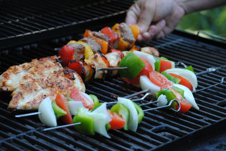 Cropped hand holding skewers on barbecue grill