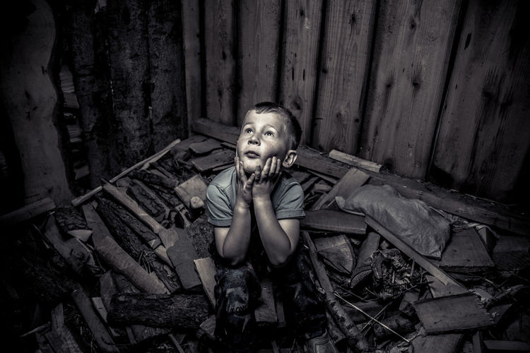 High angle view of trapped boy sitting on rubble in room