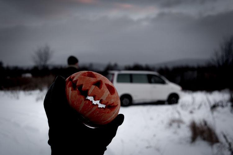 Hand holding pumpkin lantern