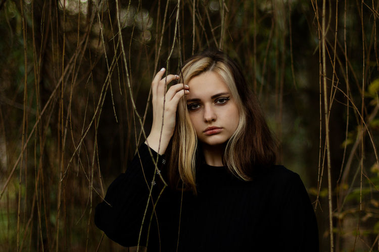 Portrait of beautiful young woman standing against plants outdoors