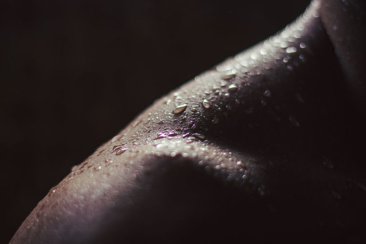 Close-up of water drops on man over black background
