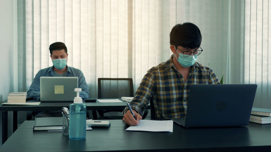 Businessmen wearing mask working in office