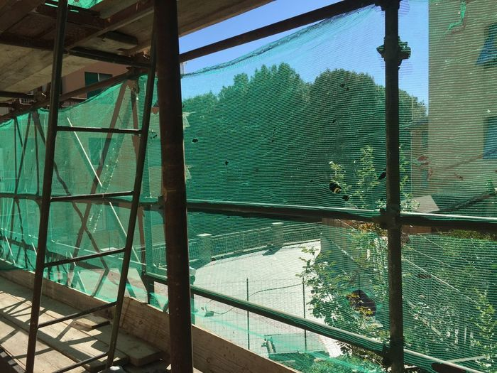 Construction site In The Progress. In The Work In The Works Façade Front Front View Work In Progress Building Site Construction Site Construction Trees Tree Built Structure Architecture Day No People Metal Outdoors Nature Security Plant Green Color Sunlight Building Fence