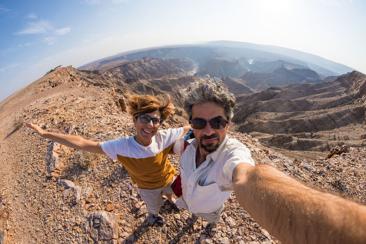Couple taking selfie at the Fish River Canyon, scenic travel destination in Southern Namibia. Fisheye view from above in backlight. Adventure Fun Happiness Landscape Lifestyles Looking At Camera Love Men Mountain Outdoors Photographing Photography Themes Portrait Self Portrait Photography Selfie Smiling Sunglasses Sunlight Togetherness Travel Two People Vacations Young Adult Young Men Young Women