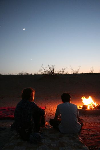 Rear view of men sitting by bonfire against sky at sunset