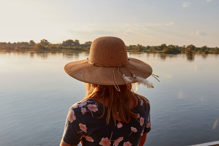 Woman with a big hat watching the sunset at the okavango river