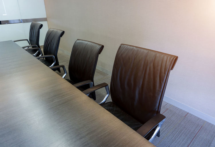 Empty chairs in conference room at office