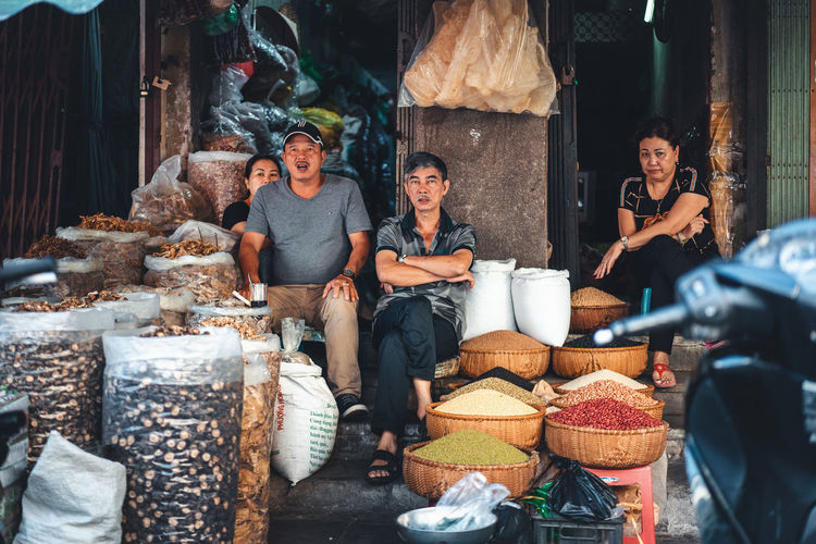 People sitting at market stall