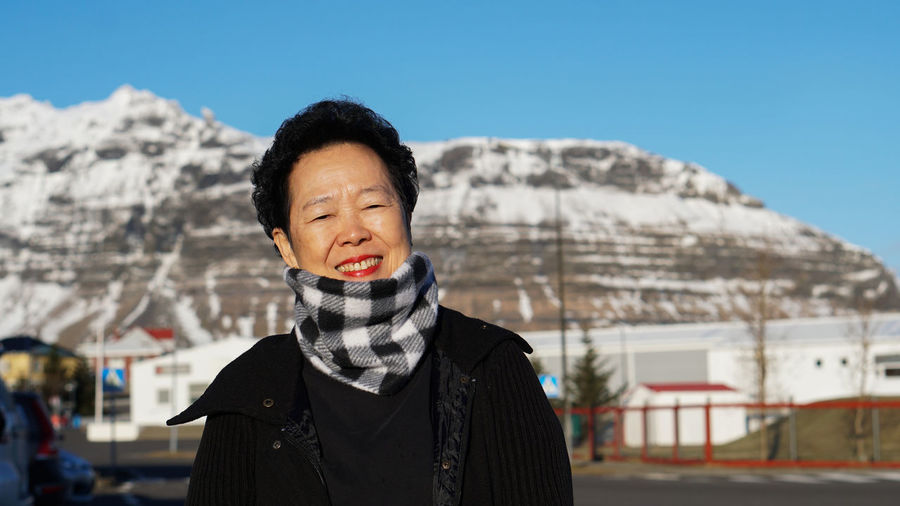 Portrait of woman standing against mountain during winter