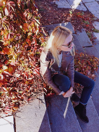 High angle view of woman sitting by autumn leaves