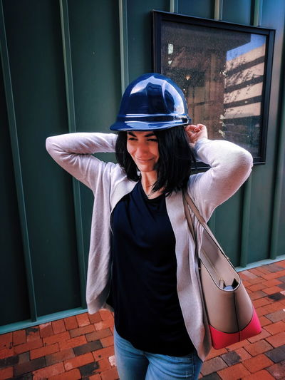 Young woman wearing hardhat against built structure