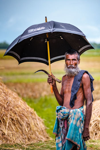 Portrait of shirtless man in field