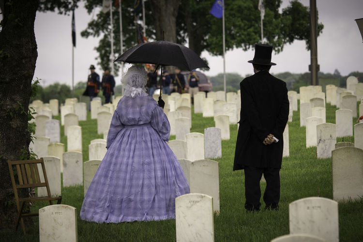 Antique Memorial Memorial Day Cemetery Clothing Emotion Grave Gravestone People Real People Rear View Standing Umbrella Women