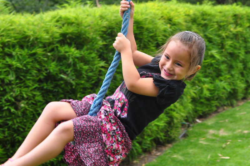 Girl swinging on rope against plants in yard
