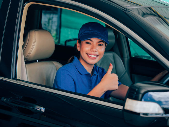 Portrait of female mechanic gesturing while sitting in car