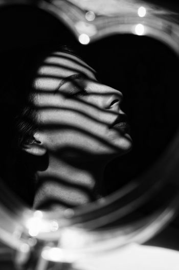 Close-Up Of Young Woman Reflecting On Mirror