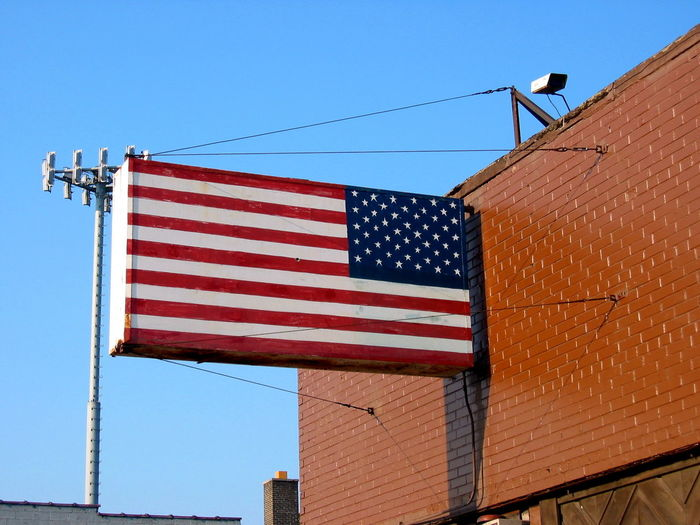Low Angle View Of American Flag Attached To Building Against Clear Blue Sky