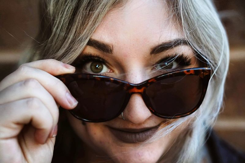 Close-up portrait of young woman wearing sunglasses