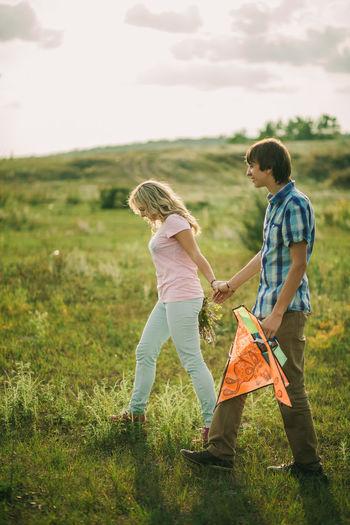 Couple walking on field against sky