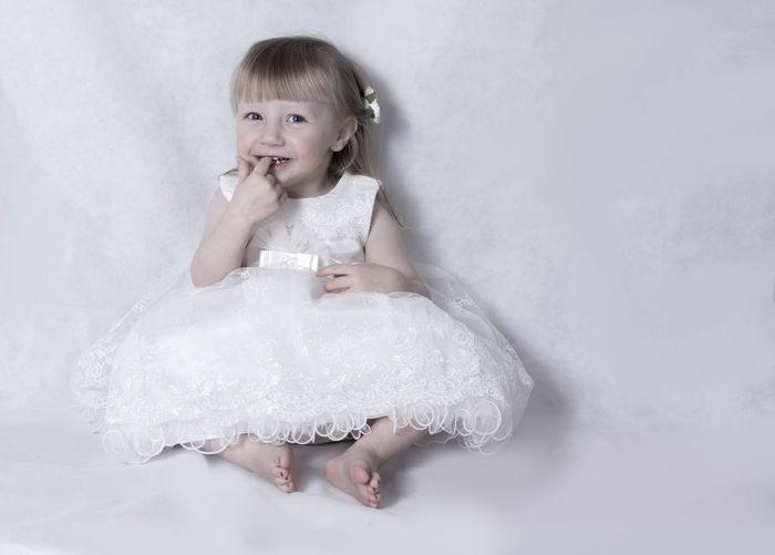Portrait Of Cute Little Girl In White Dress Sitting On White Background