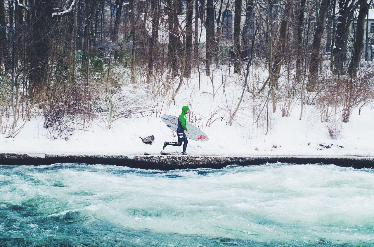 Full length of surfer running by river during winter
