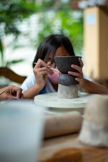Girl making pot on pottery wheel