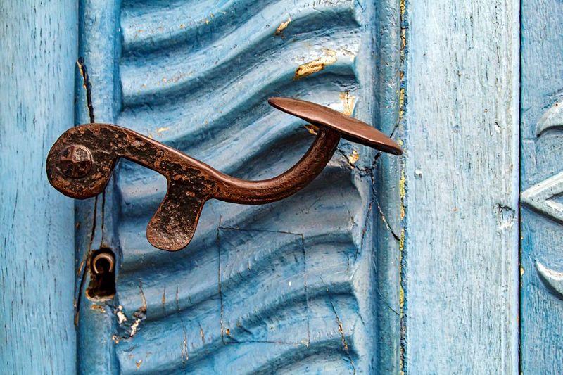 Close-up of rusty handle on blue door