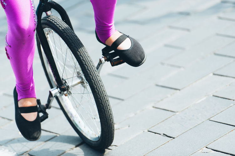 Low section of woman riding bicycle on street