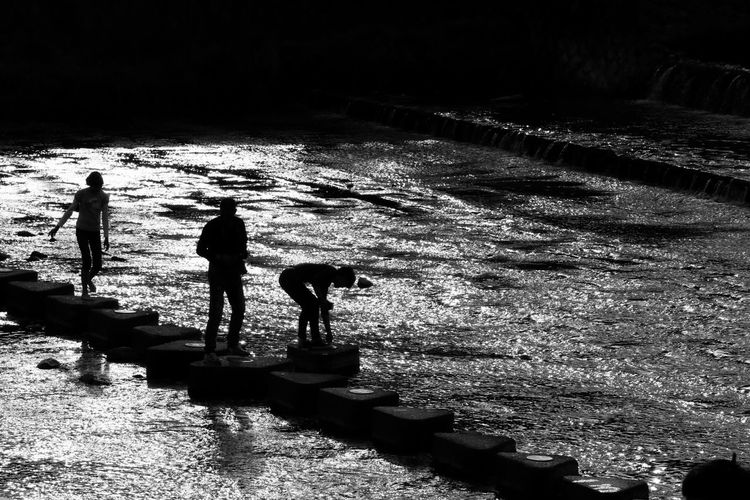 Silhouette people walking on stepping stones at kamo river