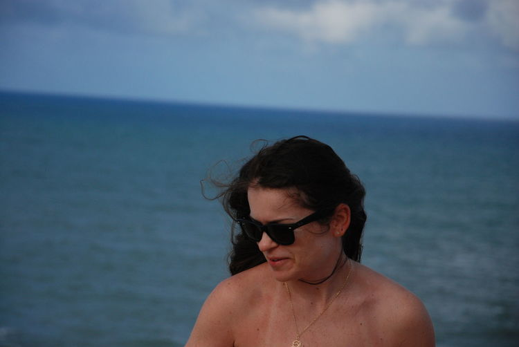 Close-up of woman wearing sunglasses standing against sea