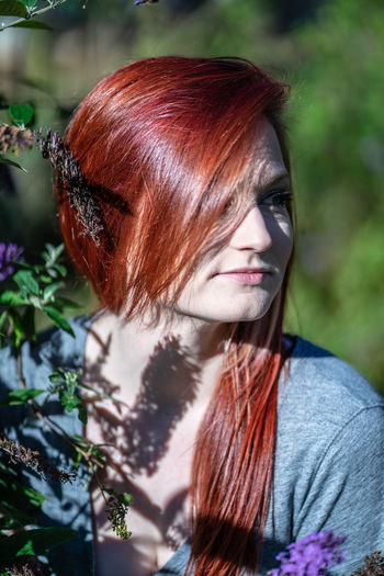 Close-Up Of Redhead Woman Looking Away In Sunny Day