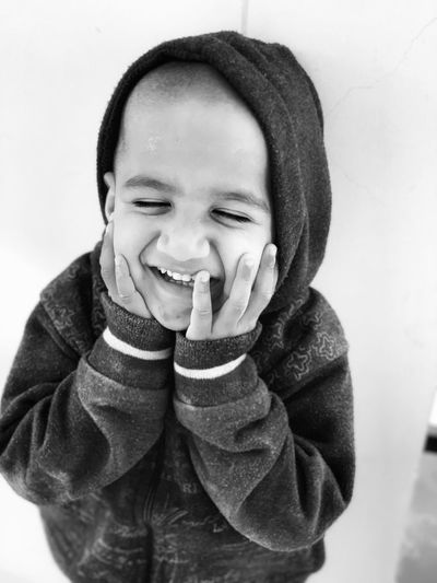 Smiling boy with hands on cheeks against wall
