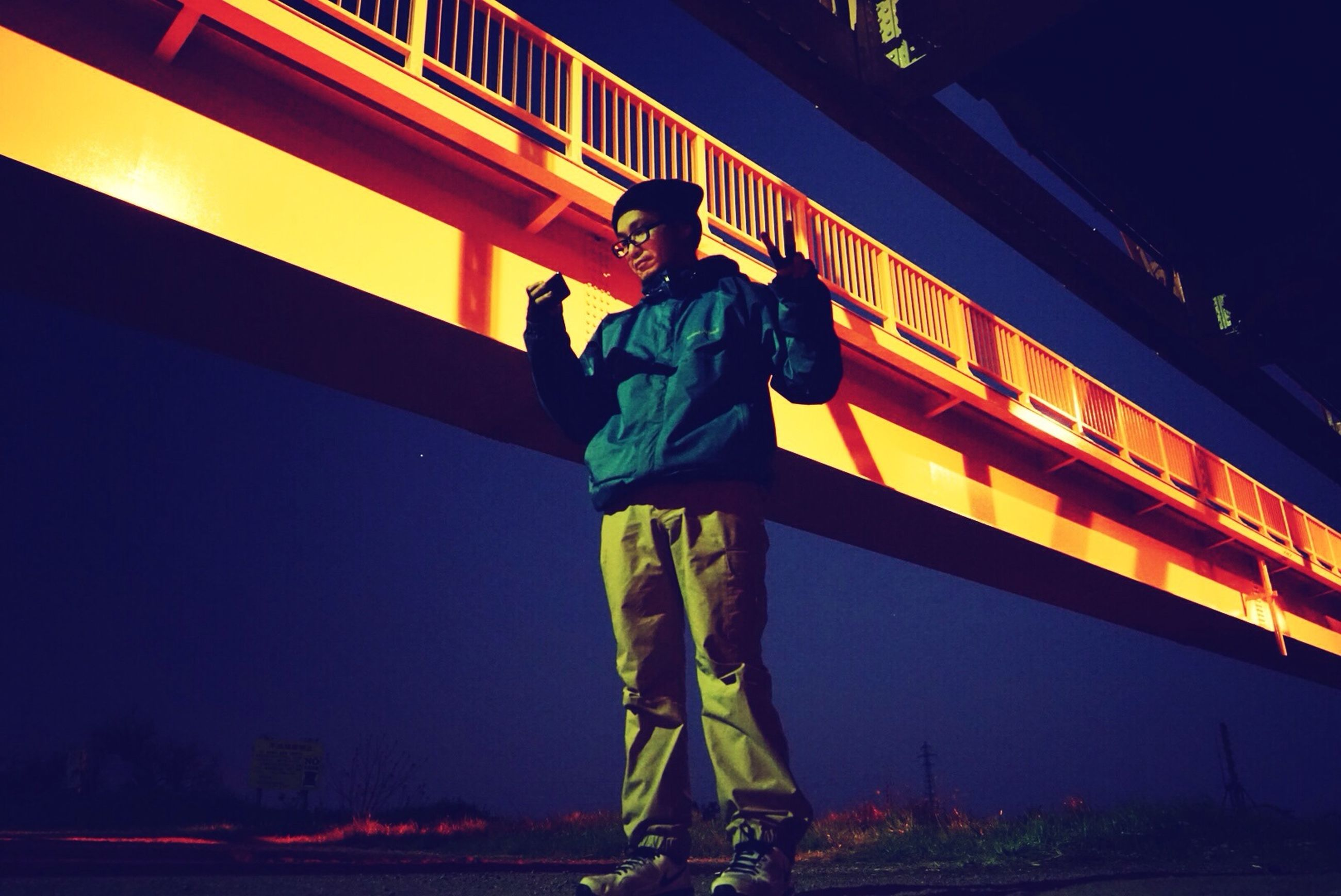 lifestyles, men, leisure activity, standing, full length, low angle view, built structure, casual clothing, rear view, architecture, night, railing, bridge - man made structure, illuminated, person, yellow, transportation, travel