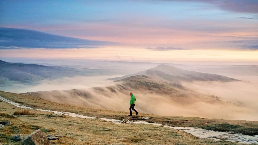 Side view of man walking on mountain against sky during sunset