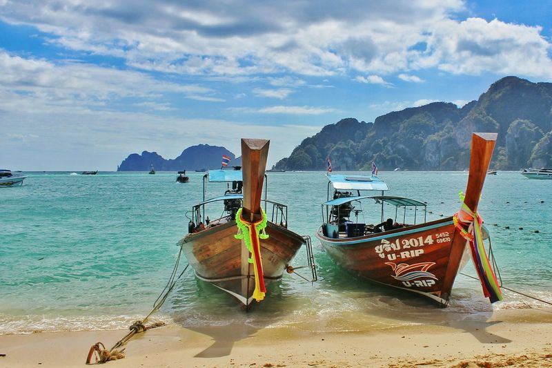 Longtail boats moored on shore against sky