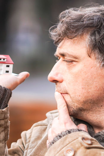 Close-up of man holding model house in city
