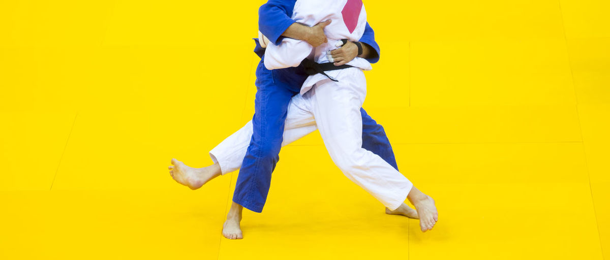 Low section of people practicing martial arts against yellow background