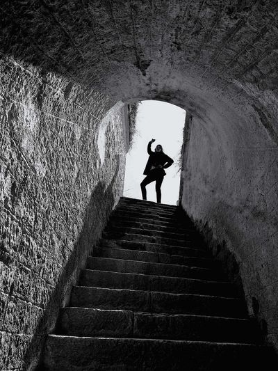 Low angle view of silhouette young woman standing on steps
