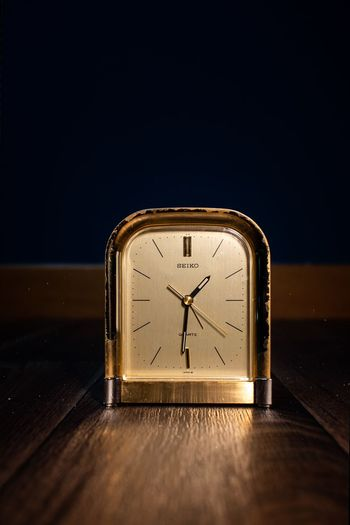 Close-up of clock on table against dark background