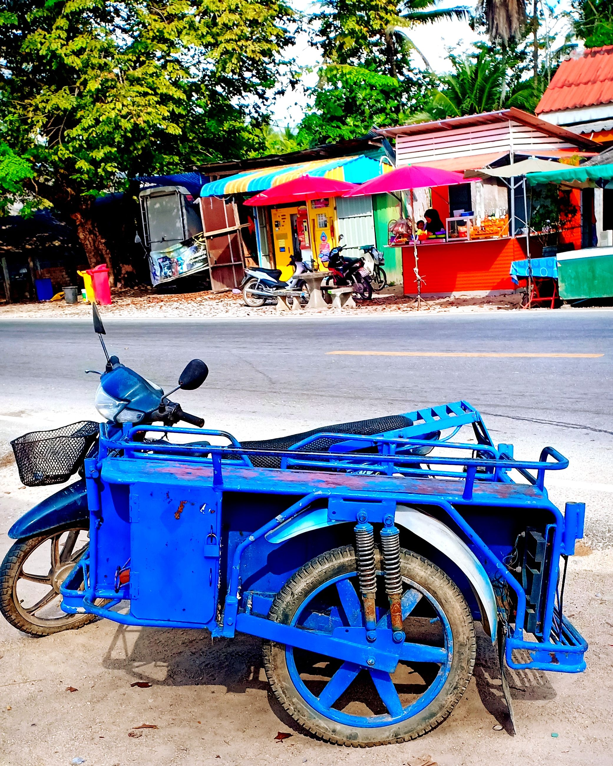 transportation, mode of transportation, city, street, architecture, land vehicle, incidental people, day, stationary, building exterior, road, outdoors, built structure, nature, tree, blue, car, rickshaw, motor vehicle, wheel