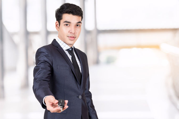 Portrait of young businessman holding car key