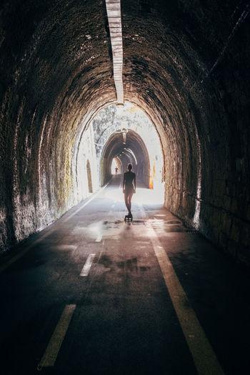 Rear view of silhouette woman skateboarding in tunnel