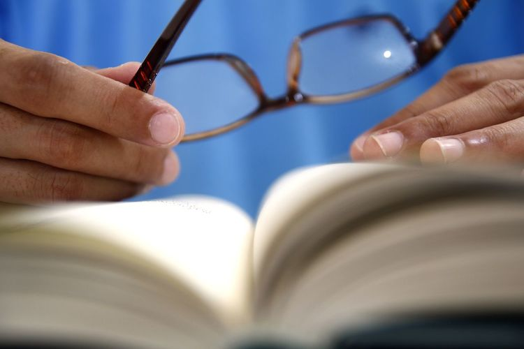 Close-up of hand holding eyeglasses on book