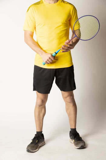 Full length of man standing against yellow background