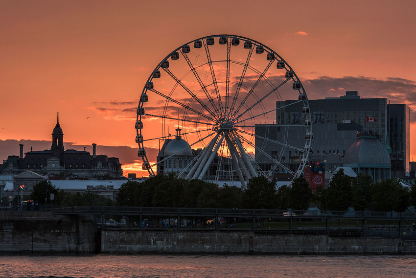 Montreal Observation Wheel Montreal Observation Wheel Montreal, Canada Montréal Amusement Park Architecture Building Exterior Built Structure Canada City Cityscape Clouds And Sky Day Ferris Wheel Nature No People Orange Color Outdoors Sky Sunset Water
