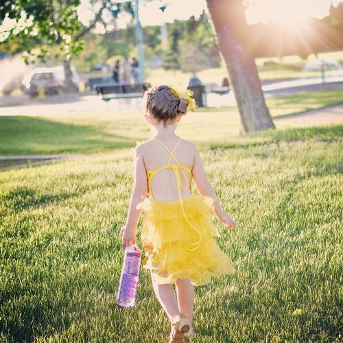 After the dance recital Childhood Day Field Focus On Foreground Full Length Grass Happiness Leisure Activity Lifestyles Nature One Person Outdoors People Real People Rear View Standing Sunlight Tree Walking Yellow Color