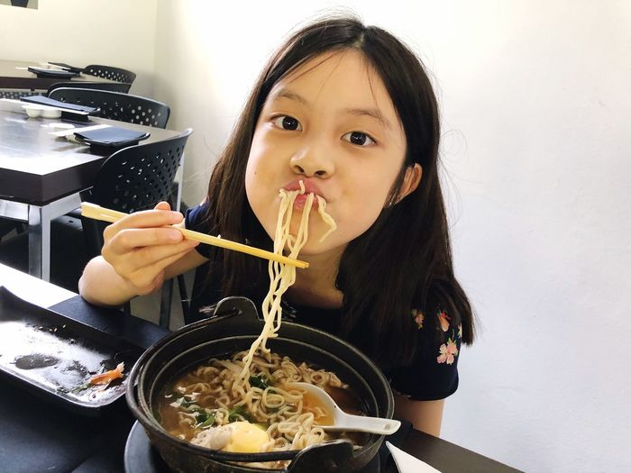 Close-Up Portrait Of Girl Eating Noodles Soup At Table
